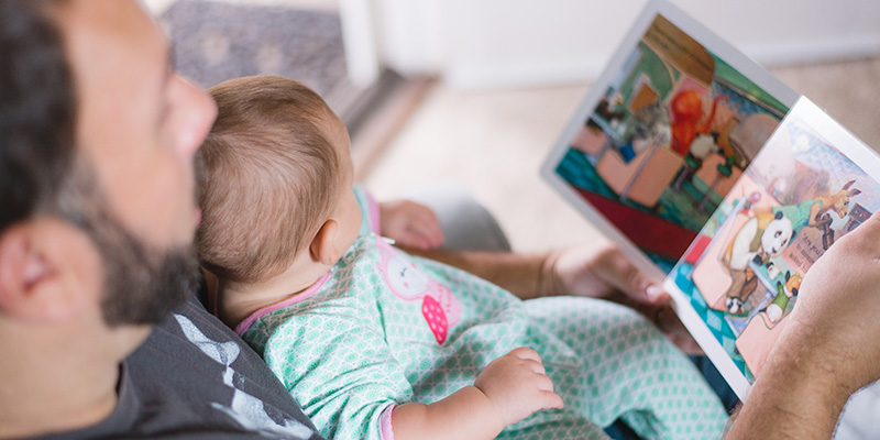 Close-up of dad reading a book to his baby